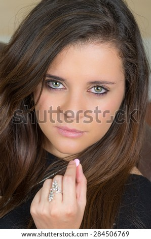 pretty brunette with beautiful eyes holding an orange pill between fingers looking into camera - stock photo