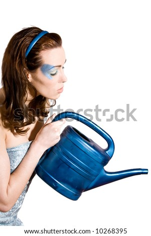 Pretty brunette with blue eyeshadow watering the plants with a blue watering can - stock photo