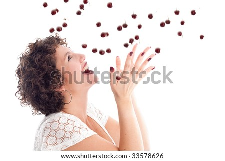 Pretty brunette with curls catching a drop of cherries