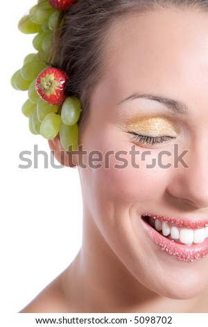 Pretty brunette with fruit (grapes and strawberries) in her hair laughing with sugar on her lips - stock photo