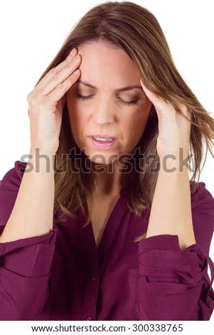 Pretty brunette with headache on white background - stock photo