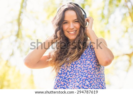 Pretty brunette with headphones on a sunny day - stock photo