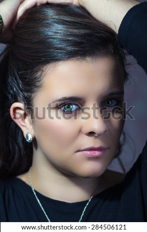 pretty brunette with intense eyes closeup looking into camera with serious expression - stock photo