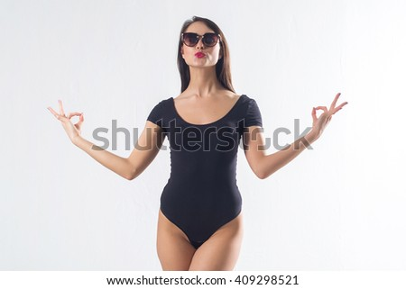 Pretty brunette with long hair, wearing black one piece swimwear, holding hands aside, imitating meditation, making duck lips on white background, not isolated. - stock photo