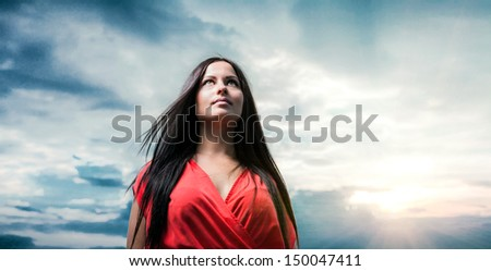 Pretty brunette with red dress posing on a dawn against evening sky . Fashion Beauty. Outdoors shot. - stock photo