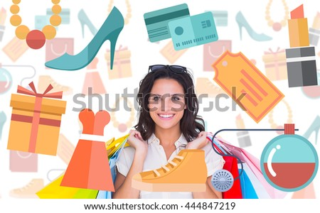 Pretty brunette with shopping bags against digital image of shopping doodles - stock photo