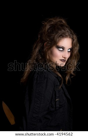 Pretty brunette with very scary eyes hiding a knife behind her back - stock photo