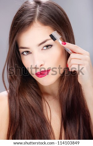 Pretty brunette woman combing her eyebrow - stock photo