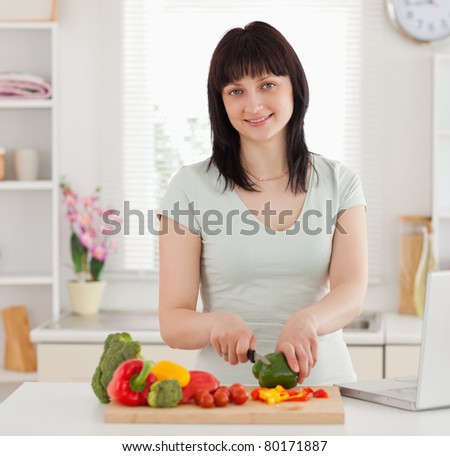Pretty brunette woman cooking while relaxing with her laptop in the kitchen
