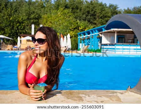 Pretty brunette woman enjoying cocktail in a swimming pool - stock photo