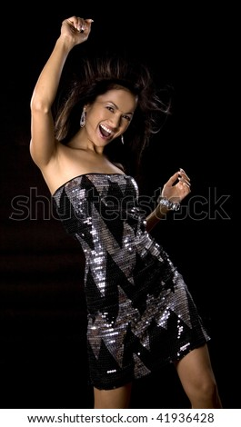 pretty brunette woman having fun on black background - stock photo