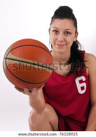 Pretty brunette woman holding Basketball in hand and smiling - stock photo