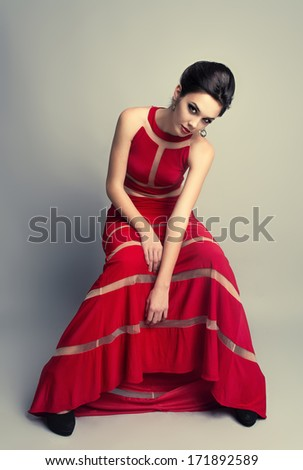 Pretty brunette woman in long evening expensive red dress. Beautiful fashion model sitting on chair in stylish modern clothing.