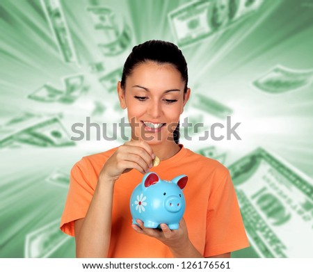 Pretty brunette woman inserting a coin in a piggy-bank isolated on white background - stock photo