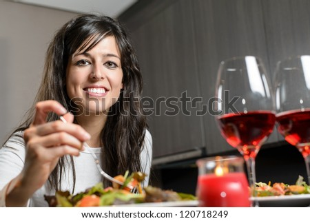 Pretty brunette woman sitting at the table smiling and eating a salad with a fork. Romantic dinner for a couple with candle and two glasses of red wine. - stock photo