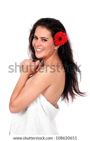 Pretty brunette woman standing naked with white towel and long hair with red Gerber flower behind ear smiling - stock photo