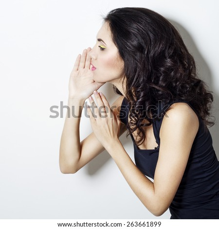 Pretty brunette woman tells someone a secret - stock photo