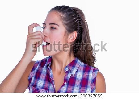 Pretty brunette woman using asthma inhaler on white background - stock photo