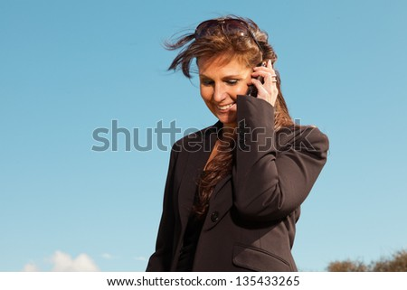 Pretty brunette woman using mobile phone. Outdoor with blue sky.