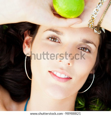 Pretty brunette woman wearing elegant dress relaxing outdoor in green grass and holding lemon or lime citrus, looking at camera with her sexy eyes