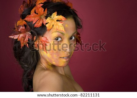pretty brunette woman wearing leaves and colorful makeup