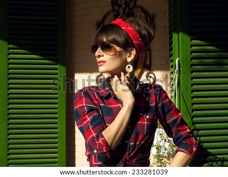 Pretty brunette woman wearing red and blue checked shirt, band, aviator sunglasses, resting in a street cafe, posing against the wall and green shutters. On a hot summer day - stock photo
