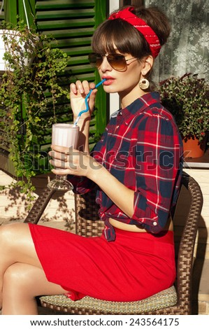 Pretty brunette woman wearing red skirt, checked shirt, band, aviator sunglasses, resting in a wickered chair in a street cafe, drinking her cold milk shake cocktail. On a hot summer day - stock photo