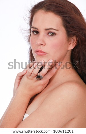 Pretty brunette woman wearing white towel or boob tube with large ring jewelery on fingers posing on white background - stock photo