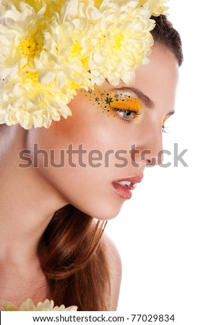 Pretty brunette woman with flower in hair and yellow makeup - stock photo