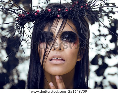 pretty brunette woman with make up like demon at halloween, closeup in wreath - stock photo