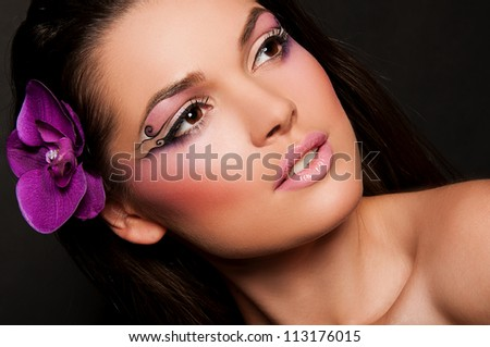 pretty brunette woman with orchid in hair