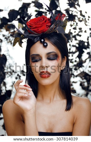 pretty brunette woman with rose jewelry, black and red, bright make up kike a vampire queen closeup halloween - stock photo