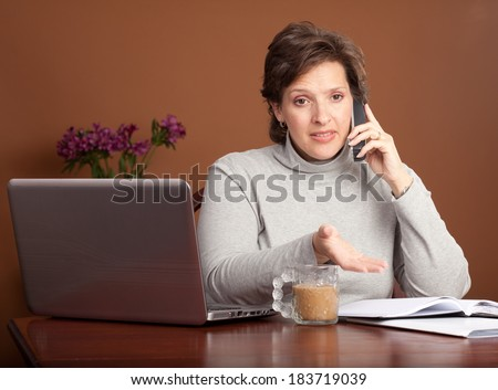 Pretty brunette working or shopping at a laptop on the kitchen table with a cup of coffee talking on the phone looking worried and gesturing with her hand - stock photo