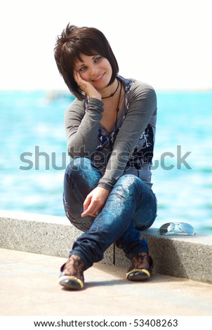 Pretty brunette young girl near the sea - stock photo