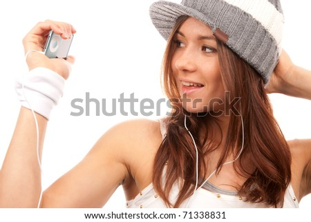 Pretty brunette young woman listening dance music in headphones on and holding mp3 player mobile isolated on a white background - stock photo