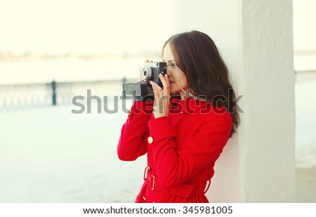 Pretty brunette young woman with retro vintage camera in winter day - stock photo