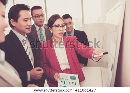 Pretty business lady explaining diagram to her colleagues - stock photo