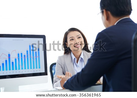 Pretty business lady explaining statistics chart to her coworker