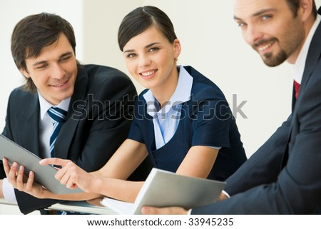 Pretty business lady looking at camera with smile surrounded by her co-workers