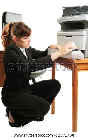 Pretty business lady or student clearing a printer paper jam. - stock photo