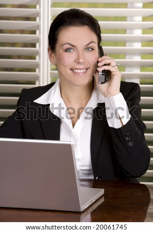 pretty business woman on the phone using laptop