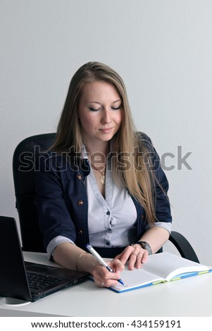 Pretty business woman portrait. Smiling young business woman sitting at her workplace in office. Face of happy business woman. Modern beautiful business woman against white background.  - stock photo