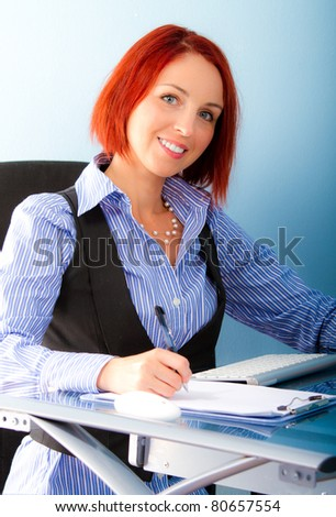 Pretty business woman sitting at table with notebook - stock photo