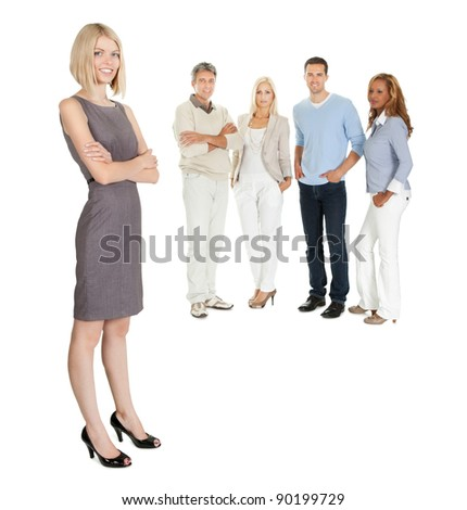 Pretty business woman standing with colleagues at the back on white - stock photo