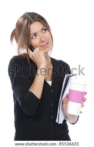 Pretty business woman talking on the mobile phone with notebook organizer  and coffee cup in hand