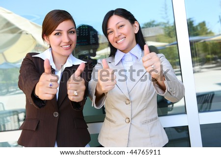 Pretty Business Woman Team at Office Building with Thumbs Up - stock photo