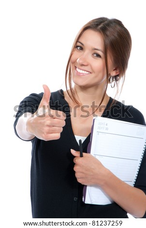 Pretty business woman thumb up, smiling, holding notepad, copy-book and a pen in office on a white background - stock photo