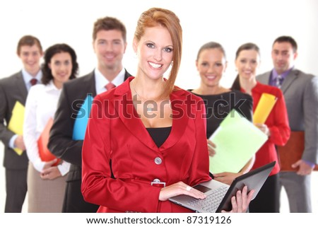 Pretty business woman with colleagues in the back - stock photo