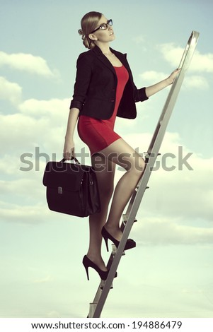 pretty business woman with work bag stepping ladder of the success with ambition  - stock photo