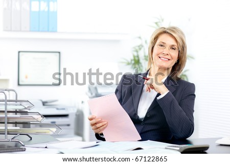 Pretty business woman working in the office - stock photo